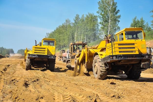Travaux routiers un grattoir de tracteur jaune nivelle le sol
