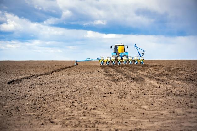 Travaux de semis au champ au printemps. tracteur avec semoir.
