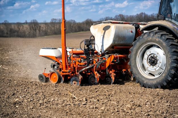Travaux de semis dans le champ. tracteur avec semoir.
