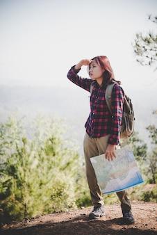 Traveller girl recherche la bonne direction sur la carte, en voyageant en randonnée dans la montagne. concept de voyage.