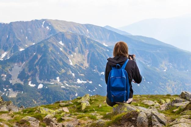 Travels est assis au sommet d'une montagne et prend des photos du paysage de montagne vert
