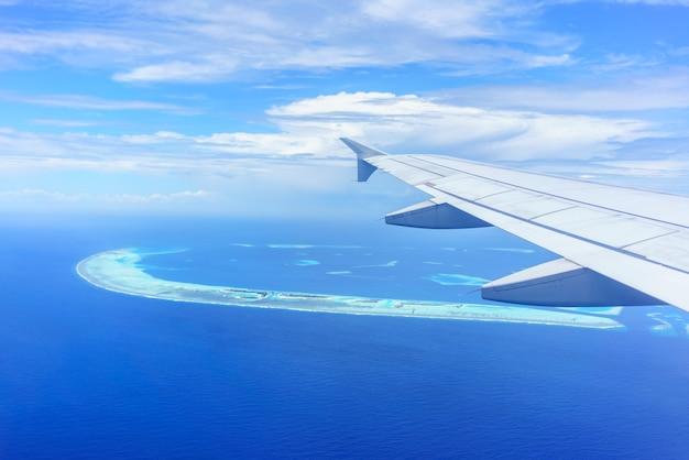 À travers la fenêtre de l'avion en voyant l'aile de l'avion nuages blancs ciel bleu et îles maldives