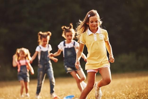 À travers les obstacles. les enfants courent sur le terrain en journée ensoleillée. conception d'un mode de vie sain.
