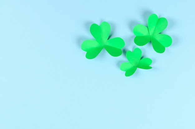Trèfle vert bricolage st. patricks day sur fond bleu.