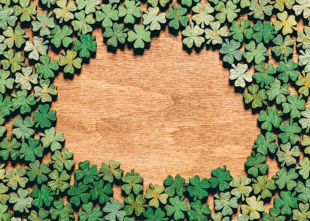 Trèfles à quatre feuilles portant sur le plancher en bois