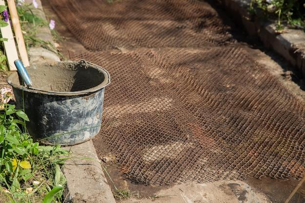 Treillis métallique posé au sol pour cimenter les allées du jardin.