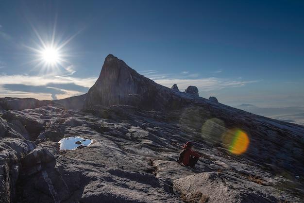 Trekker assis sur la montagne kinabalu avec le pic sud