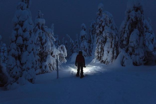 Trekker avec une lampe frontale marchant dans un parc national enneigé de riisitunturi, finlande