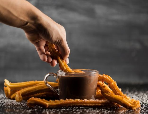 Tremper des churros dans une tasse remplie de chocolat fondu