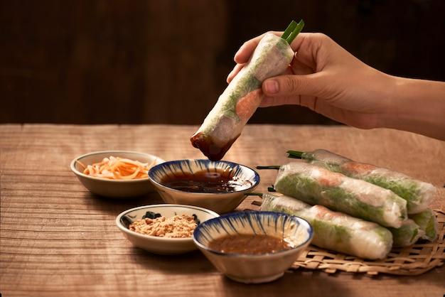 Tremper à la main des rouleaux de papier de riz végétarien dans la sauce soja