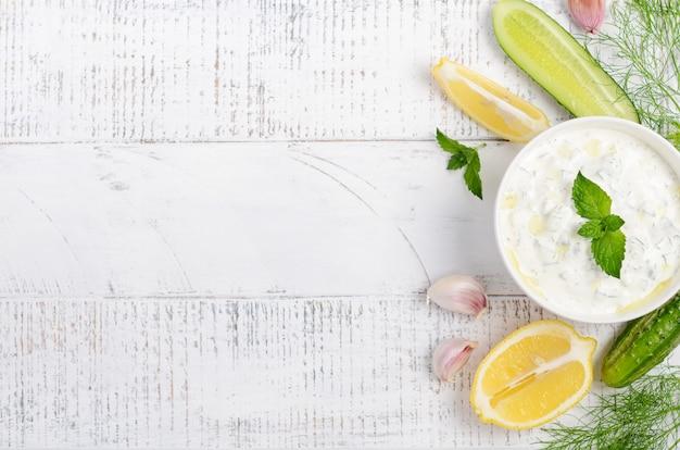 Trempette grecque ou vinaigrette tzatziki et ingrédients décorés à l'huile d'olive et à la menthe sur une table en bois blanche