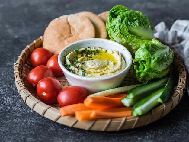 Trempette de houmous à tartiner traditionnelle faite maison servie avec des légumes frais, du pain pita et des herbes