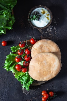 Trempette libanaise au fromage à la crème avec de l'huile d'olive, des épices et des herbes avec du pain pita, des tomates et de la laitue.