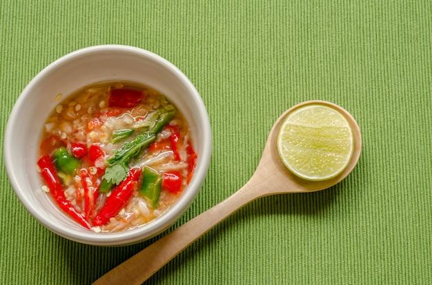 Trempette thaïlandaise épicée aux fruits de mer sur fond vert