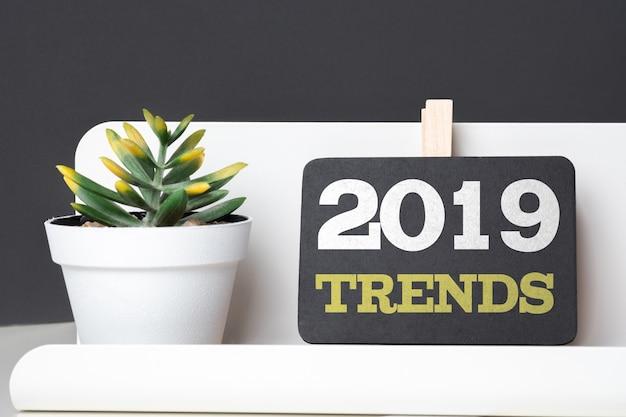 Trends 2019 sur tableau noir avec une boîte à crayons moderne et une plante verte