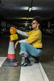 Trendy hipster femme noire accroupie près du cône de signalisation