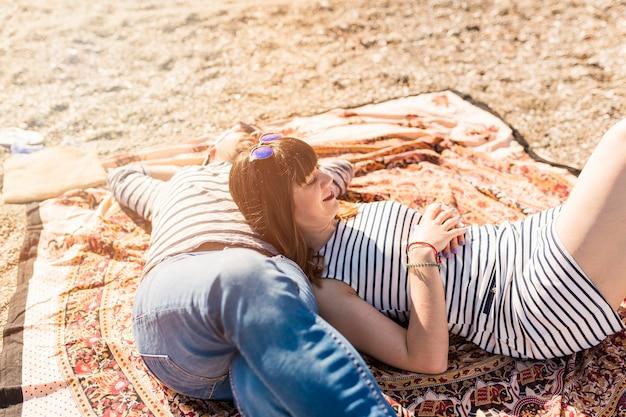 Trendy jeune couple allongé sur la couverture à la plage