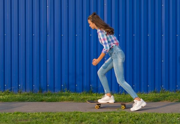 Trendy jeune femme mince avec de longs cheveux bruns skateboard au crépuscule le long d'un chemin urbain en face d'un mur bleu