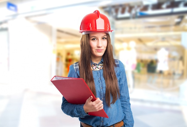 Trendy jeune femme tenant un dossier rouge et coiffé d'un casque