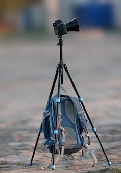 Un trépied solitaire et un sac à dos de photographe accroché dessus sont photographiés tôt le matin sur un site vide
