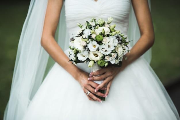 Très beau bouquet de mariée entre les mains de la mariée