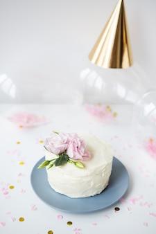 Très beau petit gâteau blanc décoré de fleurs naturelles eustoma sur fond bonbon, ballons, casquette. notion de vacances.