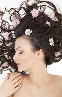 Très belle fille allongée avec des fleurs aux cheveux brillants dans ses cheveux maquillage lumineux isolé sur blanc
