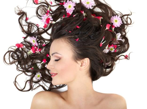 Très belle fille allongée avec des fleurs rouges vives dans ses cheveux maquillage lumineux isolé sur blanc