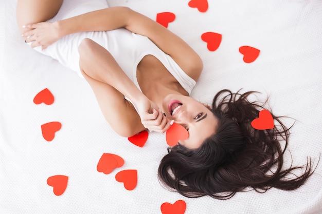 Très belle jeune femme allongée sur le lit. vue de dessus de jolie fille avec des coeurs en papier