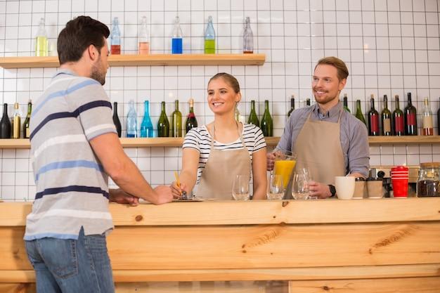 Très bon service. joyeux gentils jeunes debout au comptoir et écoutant le client tout en travaillant à la cafétéria