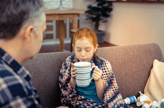 Très chaud. jolie fille mignonne soufflant dans le thé tout en tenant une tasse dans ses mains