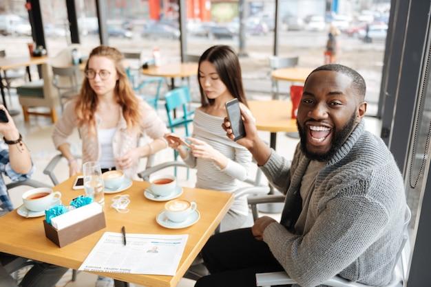 Très émotif. jeune beau mec exprime son bonheur entouré de ses amis à la cafétéria.