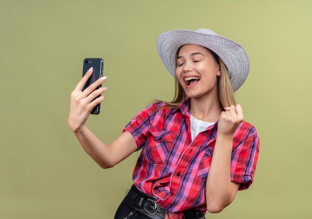 Une très heureuse belle jeune femme dans une chemise à carreaux à la recherche de téléphone mobile tout en levant le poing fermé
