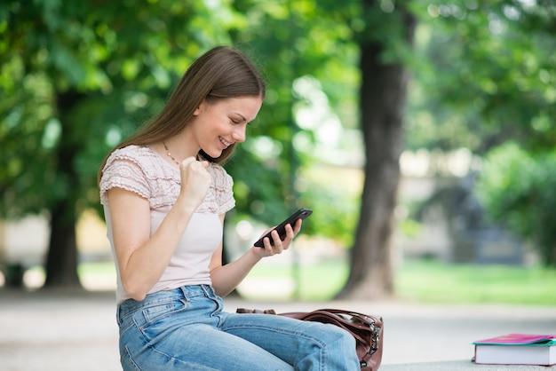 Très heureuse femme regardant son téléphone portable