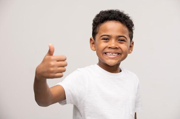 Très heureux mignon petit garçon touchant la tête par les mains et criant pour exprimer sa surprise avec de bonnes nouvelles inattendues
