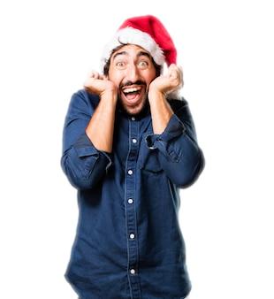 Très heureux avec les poings soulevé l'homme et le chapeau de santa
