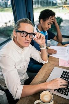 Très intelligent. homme intelligent intelligent fixant ses lunettes alors qu'il était assis près de son élève