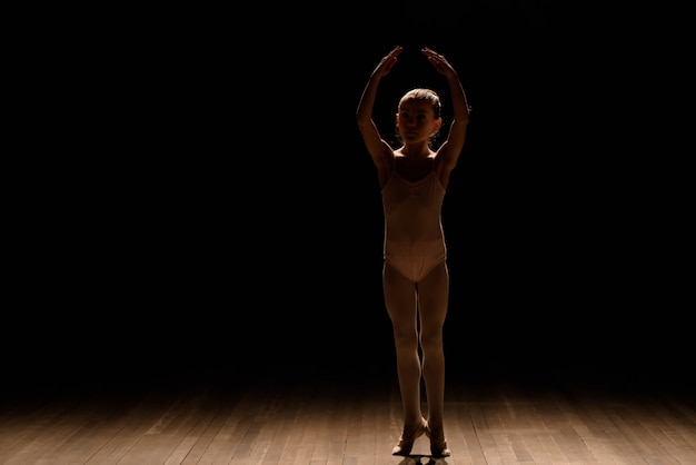 Très jeune ballerine posant sur un fond noir