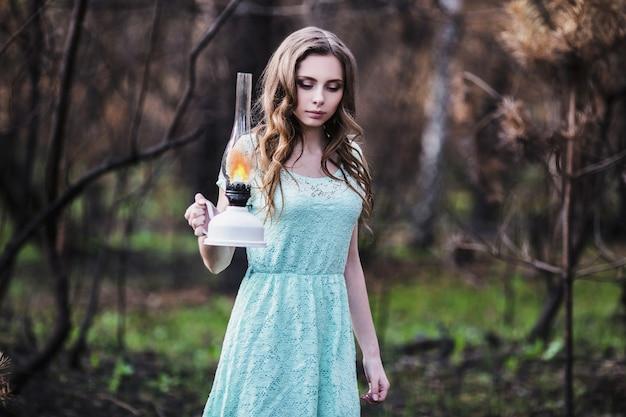 Très jolie jeune fille avec une lampe à pétrole. apparence de poupée. femme aux cheveux bruns dans une robe turquoise sur la nature. cheveux longs. lumière naturelle. modèle posant sur la nature. lampe à la main. perdu dans la forêt
