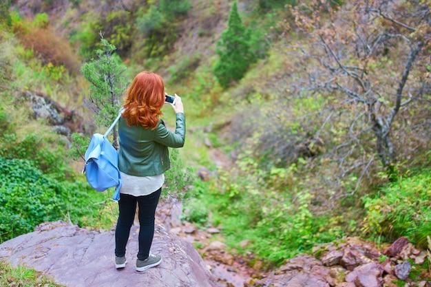 Très jolie randonneuse enregistre un vlog vidéo pour sa chaîne dans la forêt de montagne.