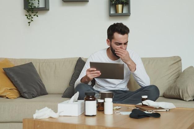 Très malade jeune homme avec tablette numérique assis sur un canapé et couvrant sa bouche tout en toussant pendant le travail à distance dans l'environnement familial