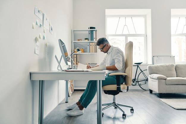 Très occupé. beau jeune homme écrivant quelque chose alors qu'il était assis au bureau