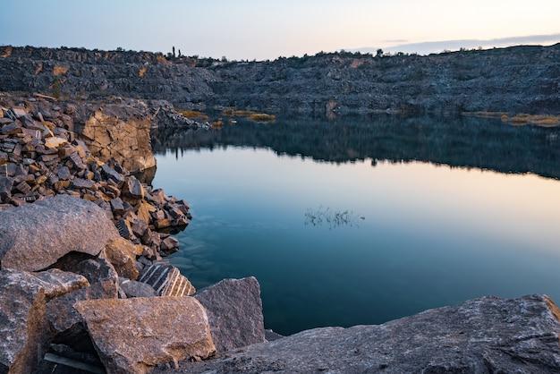 Un très petit lac magnifique entouré de grands tas de déchets de pierre du travail acharné dans la mine