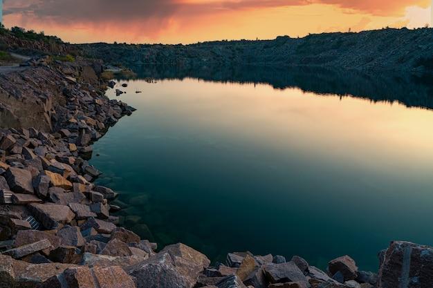 Un très petit lac magnifique entouré de gros tas de déchets de pierre du travail acharné dans la mine