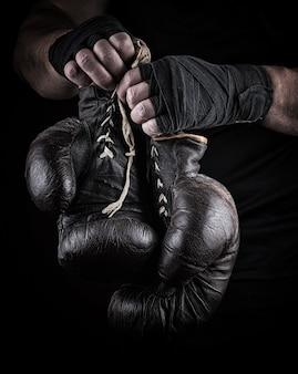 Très vieux gants de sport de boxe dans les mains des hommes