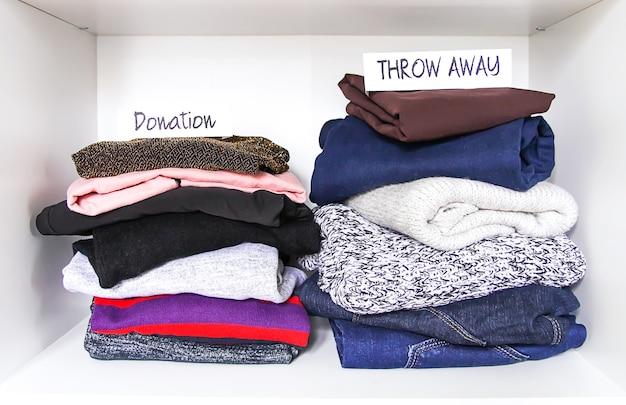 Tri des vêtements dans la garde-robe de la maison sur fond d'étagère blanche. don, jetez les notes papier.