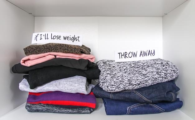 Tri des vêtements dans la garde-robe de la maison sur fond d'étagère blanche. jetez, si je vais perdre du poids, des notes de papier.