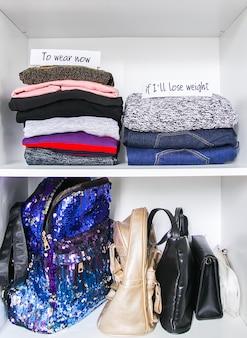 Tri des vêtements dans la garde-robe de la maison sur fond d'étagère blanche. a porter maintenant, si je vais perdre du poids, des notes en papier.