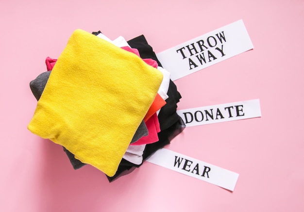 Tri des vêtements dans la garde-robe de la maison pour le don, le port et le rejet avec des notes en papier sur fond rose tendre.