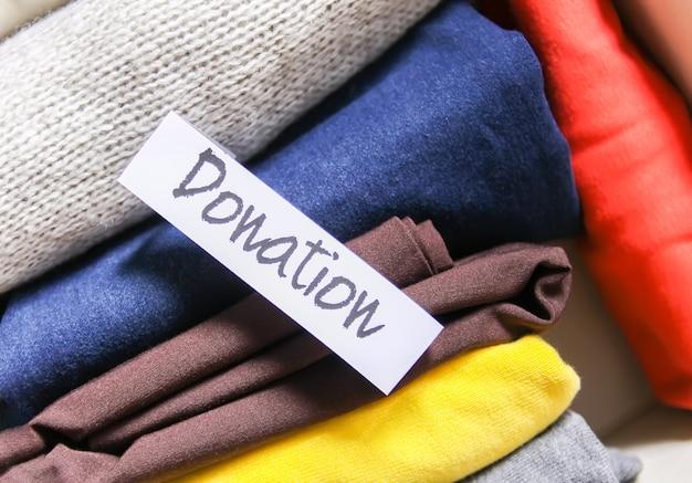 Tri des vêtements dans le stockage vertical de la garde-robe de la maison pour le don avec une note papier sur fond rose tendre.